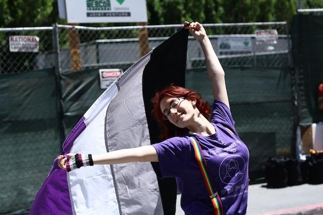 Aseksüelliğin resmi bayrağını taşıyan genç eylemci (Kaynak: www.vice.com)