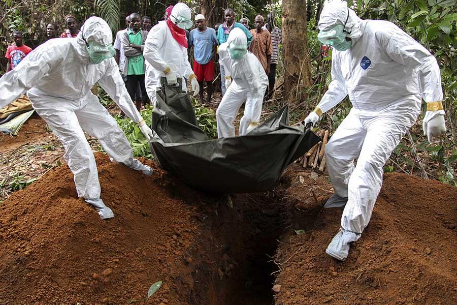 Liberyalı hemşireler, Ebola'dan yaşamını kaybeden bir insanın cesedini yakmak üzereyken. (Fotoğraf: EPA)
