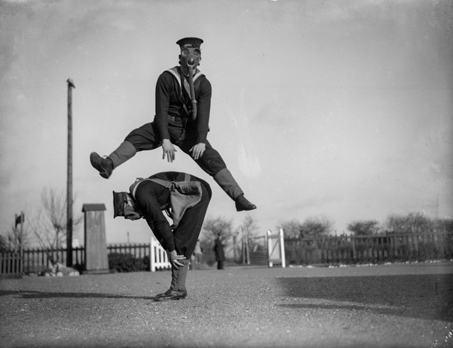 22nd January 1934: Able seamen at the Royal Navy Anti-Gas School at Tipnor, Portsmouth play leapfrog wearing gas masks, to accustom them to carrying out strenuous tasks in respirators. (Photo by William Vanderson/Fox Photos/Getty Images)