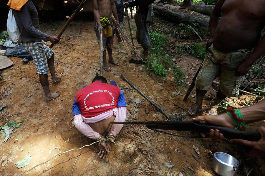 Ka'apor savaşçıları yakalayıp bağladıkları ormancının başında bekliyor (Fotoğraf: Lunae Parracho/Reuters)