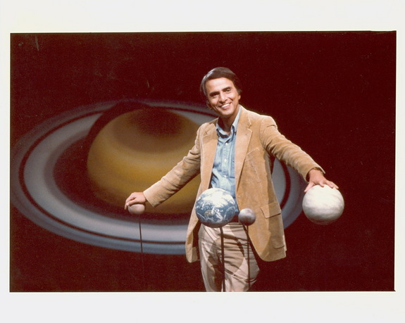 Carl Sagan standing with hands on globes of planets. Photo by Eduardo Castaneda
