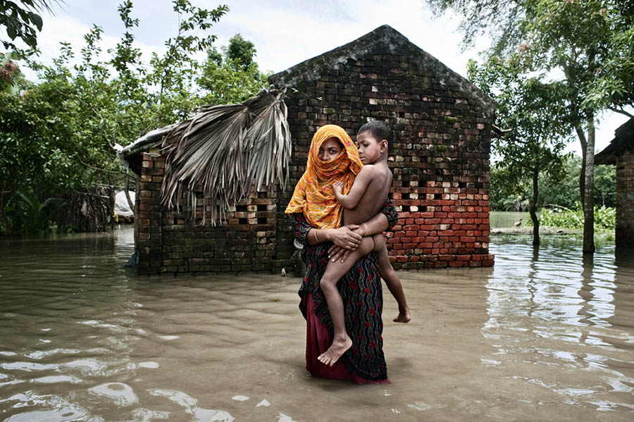 Bangladesh, Satkhira district. A woman carrying her son in the flooded village of Debnagar; in the background her flooded house.