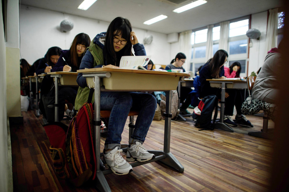 """Students sit the annual Scolastic Aptitude Test at a the Poongmun high school in Seoul on November 13, 2014. South Korea went into """"hush"""" mode, as nearly 650,000 students sat the annual college entrance exam that will play a large part in defining their adult lives in an ultra-competitive society. AFP PHOTO / Ed Jones (Photo credit should read ED JONES/AFP/Getty Images)"""