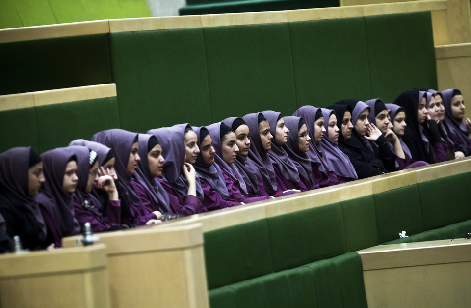 Iranian school girls observe Members of Parliament (MP) discussing a draft to limit photographer's and cameramen's access to cover parliament's open sessions in Tehran on February 27, 2013. The debate took part on the sidelines of a parliamentary session to discuss the annual budget bill which is being presented by the government. AFP PHOTO/BEHROUZ MEHRI (Photo credit should read BEHROUZ MEHRI/AFP/Getty Images)