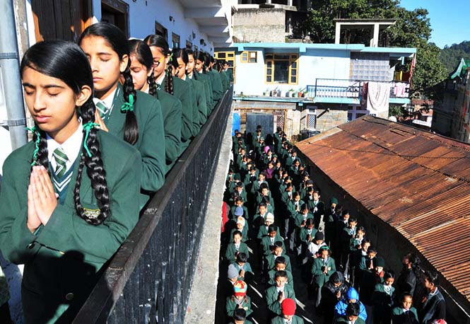 Indian schoolchildren pray during morning assembly at their school in Shimla on December 17, 2014, as they pay tribute to slain Pakistani schoolchildren and staff after an attack on an army school in the restive city of Peshawar. Pakistan began three days of mourning on December 17, for the 132 schoolchildren and nine staff killed by the Taliban in the country's deadliest ever terror attack as the world united in a chorus of revulsion. The 141 people were killed when insurgents stormed an army-run school in the northwestern city of Peshawar and systematically went from room to room shooting children during an eight-hour killing spree. AFP PHOTO/STR (Photo credit should read STRDEL/AFP/Getty Images)