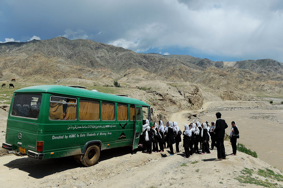 """Afghan schoolgirls board a bus in Qara Zaghan village in Baghlan province on May 7, 2013. Afghanistan's education minister has threatened to punish students over cases when schools are hit by alleged """"poisonings"""" that many officials believe are actually temporary psychological illnesses. Scores of girls' schools over recent years have seen mysterious mass fainting's, nausea and similar symptoms that are often blamed by police and media on Taliban insurgents or toxic gas leaks. AFP PHOTO/ SHAH Marai (Photo credit should read SHAH MARAI/AFP/Getty Images)"""
