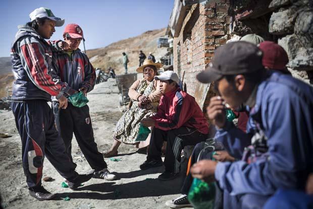Maxima evinin önünde koka yaprakları çiğneyen bir grup genç maden işçisiyle oturuyor. Koka suyunun madendeki ağır işler için onlara enerji verdiğini varsayıyorlar.