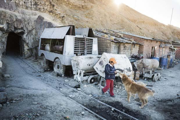 Israel maden girişinin hemen yanındaki evlerinin önünde durup altı köpeğinden biri olan Oso ile oynuyor.