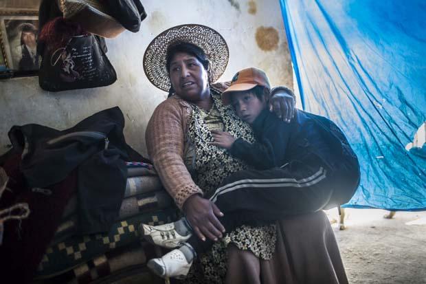 Maxima Limachi, en küçük çocuğu Israel'i kollarında tutarken. Pencere pervazında vefat etmiş eşinin fotoğrafı var. Eşi, 35 yaşındayken Cerro Rico'nun maden tünellerinin birinde geçirdiği bir kaza nedeniyle vefat etmiş. O zamandan beri, Maxima çocuklarını tek başına büyütmeye çalışıyor.